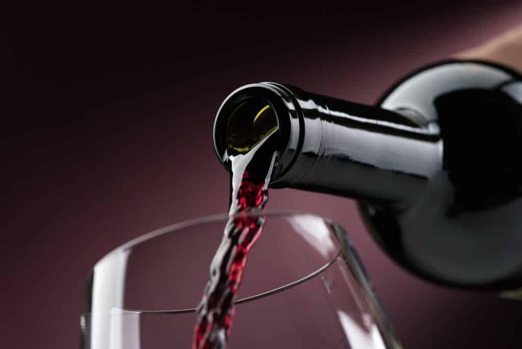 Rotwein in ein Weinglas einschenken